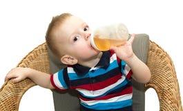 Der kleine blonde Junge sitzt in einem geflochtenen Stuhl und trinkt jui Stockfotografie