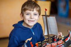 Der kleine blonde Vorschulkinderjunge, der mit Spielzeug spielt, versenden zuhause Stockfoto