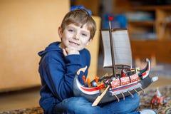 Der kleine blonde Vorschulkinderjunge, der mit Spielzeug spielt, versenden zuhause Stockfotografie