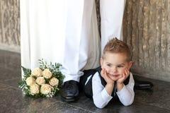 Der kleine durchdachte Junge liegt auf einem Boden mit einem Brautblumenstrauß an einer Hochzeit stockbild
