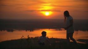 Der kleine Junge, der Badminton spielt und haben Spaß mit seiner älteren Schwester auf dem Hügel bei Sonnenuntergang stock video