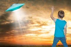 Der kleine Junge betrachtet oben einem unbekannten Flugobjekt, das im Himmel erschien Stockfotografie