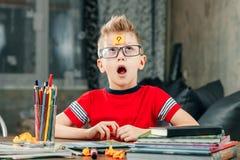 Der kleine Junge dachte und haftete einen Aufkleber auf seiner Stirn Löst das Problem stockfotografie