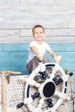 Der kleine Junge, der auf dem Kasten sitzt und halten das Lenkrad Lizenzfreies Stockbild
