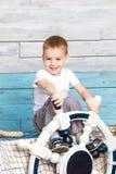 Der kleine Junge, der auf dem Kasten sitzt und halten das Lenkrad Lizenzfreie Stockfotos
