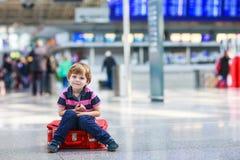 Der kleine Junge, der auf Ferien geht, lösen mit Koffer am Flughafen aus Stockfoto