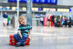 Der kleine Junge, der auf Ferien geht, lösen mit Koffer am Flughafen aus Lizenzfreie Stockbilder
