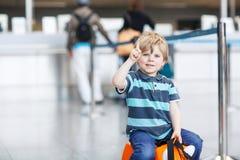 Der kleine Junge, der auf Ferien geht, lösen mit Koffer am Flughafen aus Lizenzfreies Stockbild