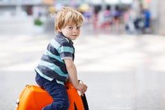 Der kleine Junge, der auf Ferien geht, lösen mit Koffer am Flughafen aus Stockfotografie