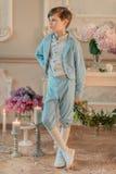 Der kleine Junge in der blauen Klage im Studio mit Blumen Stockfotografie
