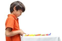 Der kleine Junge, der Domino spielt, fallen unten lizenzfreies stockfoto