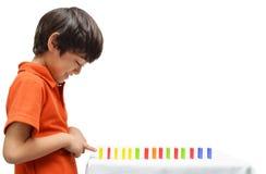 Der kleine Junge, der Domino spielt, fallen unten stockbilder
