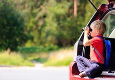 Der kleine Junge, der durch Ferngläser schaut, reisen mit dem Auto Lizenzfreies Stockfoto