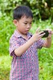Der kleine Junge, der Fotos durch Digitalkamera auf Smartphone mit macht, gehen Stockfotos