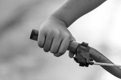 Der kleine Junge der Hand und alte Fahrradlenkstange, Schwarzweiss-Schweinestall Stockbilder