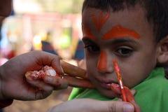 Der kleine Junge, der sein Gesicht hat, malte die Kinder, die das Spaßspielen haben Lizenzfreie Stockbilder