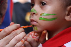 Der kleine Junge, der sein Gesicht hat, malte die Kinder, die das Spaßspielen haben Lizenzfreie Stockfotos