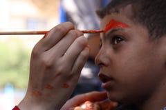 Der kleine Junge, der sein Gesicht hat, malte die Kinder, die das Spaßspielen haben Lizenzfreie Stockfotografie