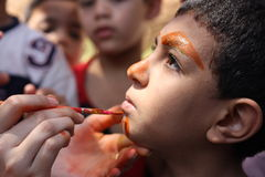 Der kleine Junge, der sein Gesicht hat, malte die Kinder, die das Spaßspielen haben Stockbild