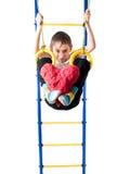 Der kleine Junge, der am Sport hängt, schellt und hält, ein rotes Herz zu treten Stockfotos