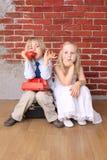 Der kleine Junge, der am Telefon spricht, Mädchen wird gebohrt stockfotos