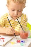 Der kleine Junge, der am Tisch sitzt, zeichnet und taucht Bürste ein lizenzfreies stockfoto