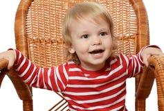 Der kleine Junge in einem Lehnsessel Stockfotos