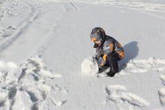 Der kleine Junge in einer Farbjacke mit einer Haube, die einen Schneeball rollt Stockbilder