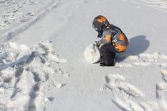 Der kleine Junge in einer Farbjacke mit einer Haube, die einen Schneeball rollt Lizenzfreie Stockfotografie