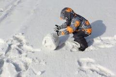 Der kleine Junge in einer Farbjacke mit einer Haube, die einen Schneeball rollt Lizenzfreies Stockbild