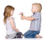 Der kleine Junge gibt dem Mädchen eine Blume Lokalisiert auf Weiß Stockbilder