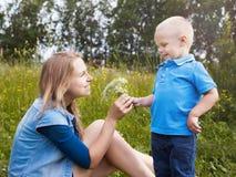 Der kleine Junge gibt zu den wilden Blumen der Mama stockbilder