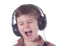 Der kleine Junge hört emotional Musik stockfotografie