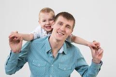 Der kleine Junge hinter seinen Vaterumarmungen stockfotos