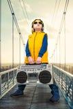 Der kleine Junge im Stil des Hip-Hop hält ein WeinleseTonbandgerät Der junge Rapper Kühlen Sie Pochen DJ ab Weinlesesilbernes Rad stockbilder