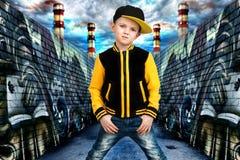Der kleine Junge im Stil des Hip-Hop Kind-` s Mode Kappe und Jacke Der junge Rapper Graffiti auf den Wänden Kühlen Sie Pochen DJ  Lizenzfreie Stockfotos