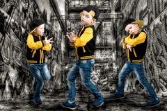 Der kleine Junge im Stil des Hip-Hop Kind-` s Mode Kappe und Jacke Der junge Rapper Graffiti auf den Wänden Kühlen Sie Pochen DJ  Stockbilder