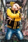 Der kleine Junge im Stil des Hip-Hop Kind-` s Mode Kappe und Jacke Der junge Rapper Graffiti auf den Wänden Kühlen Sie Pochen DJ  Stockfotos