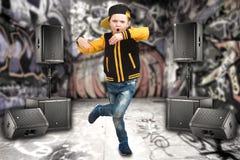 Der kleine Junge im Stil des Hip-Hop Kind-` s Mode Kappe und Jacke Der junge Rapper Graffiti auf den Wänden Kühlen Sie Pochen DJ  Lizenzfreies Stockbild