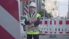Der kleine Junge im Sturzhelm-, Schutzhelm- und Uniformholdingbauplan, Kontrollearbeit Gestalt ist Geld ingenieur stock footage