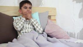 Der kleine Junge ist krank und hustet das Lügen auf dem Bett stock video