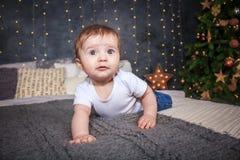 Der kleine Junge liegt auf dem Bett Ein großes Bett und einiger Weihnachtsbaum stockfotos