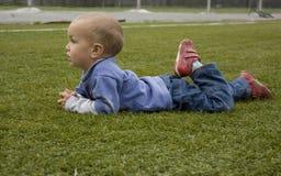 Der kleine Junge liegt auf dem Fußballplatz. Lizenzfreies Stockbild
