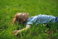 Der kleine Junge liegt auf dem Gebiet auf einem grünen Gras Lizenzfreies Stockfoto
