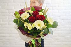 Der kleine Junge mit einem großen Blumenstrauß von Blumen stockbild