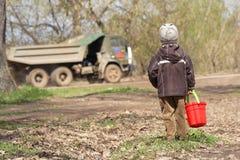 Der kleine Junge mit einer Wanne der roten Kinder Lizenzfreie Stockbilder