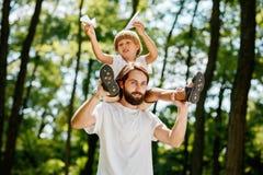 Der kleine Junge mit seinem Vater, der in den weißen T-Shirts gehend in den Waldjungen gekleidet wird, sitzt auf den Schultern vo lizenzfreies stockbild