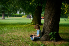 Der kleine Junge mit Tablette auf einem Schoss sitzt unter enormem Baum Stockfotografie
