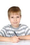 Der kleine Junge schreibt zu den Schreibenbüchern eine Kugelfeder Stockfotos