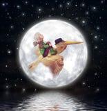Der kleine Junge und der braune Pelikan fliegen gegen den Vollmond im nächtlichen Himmel Stockbild